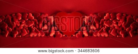 Valentine's day many red silk hearts and big heart shaped paper card background , border frame on red with copy space, love concept