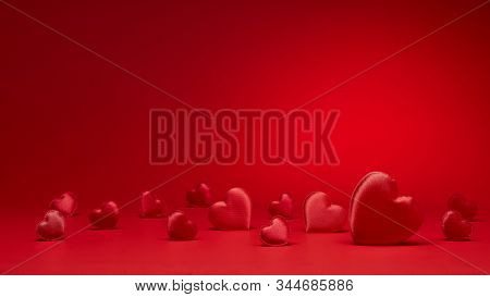 Valentine background with red silk hearts.  Valentine's Day card with copy space. Design element for romantic greeting card, invitation. Women's Day. Hearts background. Wedding day. Selective focus