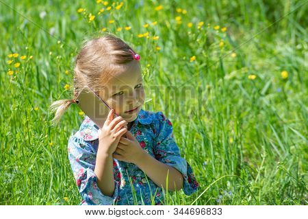Cute Little Girl Is Talking On The Phone. A Little Girl Sits With A Mobile Phone In A Green Meadow O