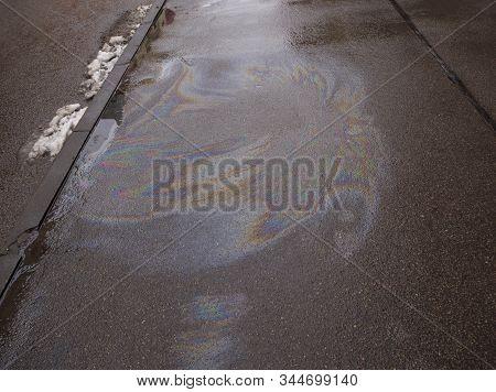Rainbow Gasoline Leak After A Car On A Pedestrian Sidewalk. Environmental Petrol Oil Pollution. Abst
