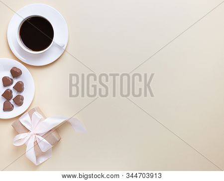 Banner Of Valentine's Day. A Cup Of Coffee, A Gift Box And A Heart-shaped Chocolate On A Neutral Bei