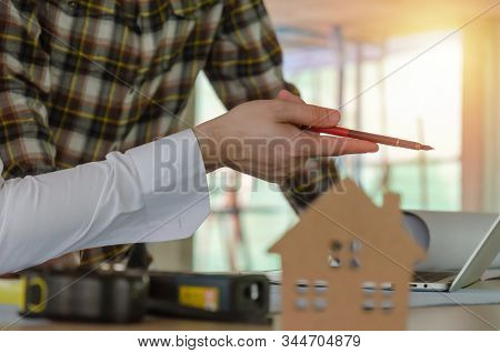 Project Manager Hand Pointing With Pen On Laptop Computer And Woooden House Model On Desk During Dis