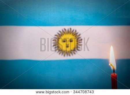 Burning Candle On The Background Of The Flag Of Argentina. The Concept Of Mourning And Sorrow In The