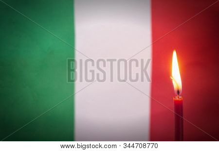 Burning Candle On The Background Of The Flag Of Italy. The Concept Of Mourning And Sorrow In The Cou