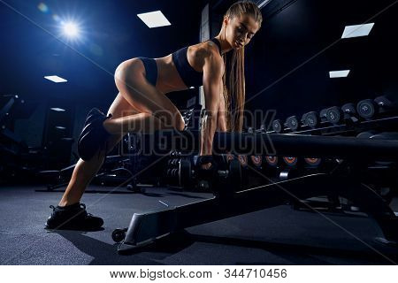 Side View Of Female Bodybuilder In Sportswear Training Back With Dumbbells. Pretty Fitnesswoman With