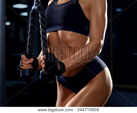 Close Up Of Strong Incognito Fitness Woman In Black Sportswear And Gloves Training Triceps. Crop Of