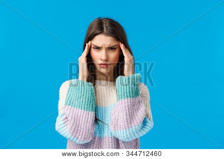 Waist-up Portrait Tensed Young Woman Feeling Unwell, Touching Temples And Squinting, Having Huge Hun