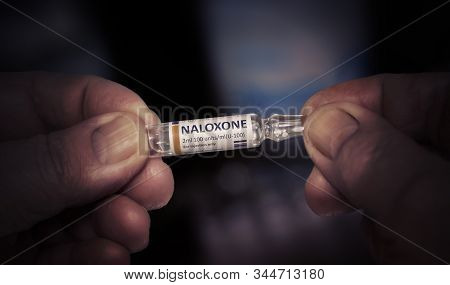 Injection Of Naloxone. Medical Ampoule In A Wrinkled Hands Of An Old Man. Healthcare Pharmacy Treatm