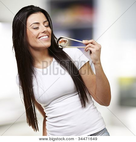 young woman eating a sushi piece, indoor