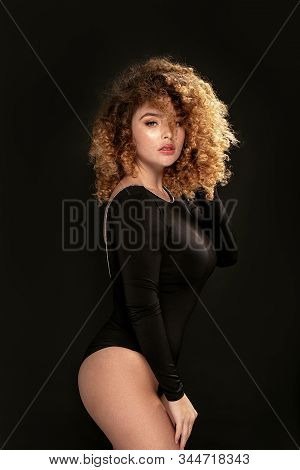 Elegant Woman With Curly Hair Posing.