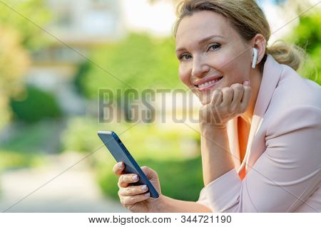 Smiling woman with smartphone on the street.  Happy businesswoman is using phone, outdoors. Cheerful businesswoman in a jacket with cell phone in park.