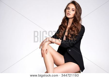 Portrait of a beautiful woman with a long hair in a black clothes. Young brunette woman in black sits on chair. Beautiful fashion model with brown hair, isolated on white background.