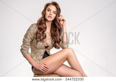 Portrait of a beautiful woman with a long hair in a golden shiny jacket. Young brunette woman in shiny sits on chair. Beautiful fashion model with brown hair, isolated on white background.