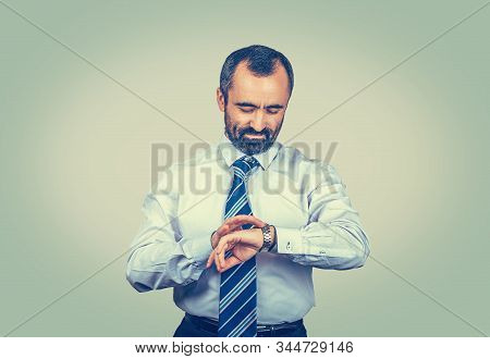 Serious Adult Bearded Man In Elegant White Shirt With Blue Tie Looking To His Watch Isolated On Ligh