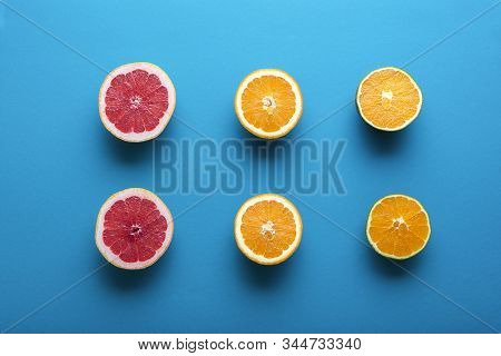 Fresh Citrus Fruits Cut In Half On Blue Background. Above View Of Halves Of Oranges, Chocolate Orang
