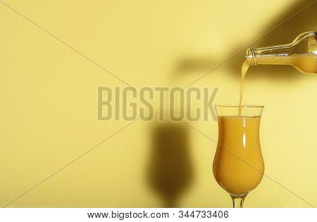 Orange Juice Poured From A Bottle Against A Yellow Background. Yellow Monotone Image With A Fresh Gl