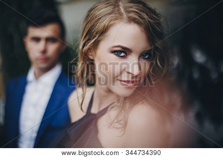 Portrait Of Stylish Couple Embracing In Rainy European City Street. Sensual Romantic Moment. Fashion
