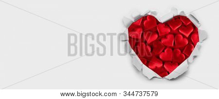 Torn white paper heart over red hearts background with copy space for text, Valentine's day love concept