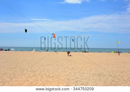Beachgoers And Kiteboarders Enjoy The Sunny Blue Skies On A Summer Day At Ottawa Beach, Holland, Mic