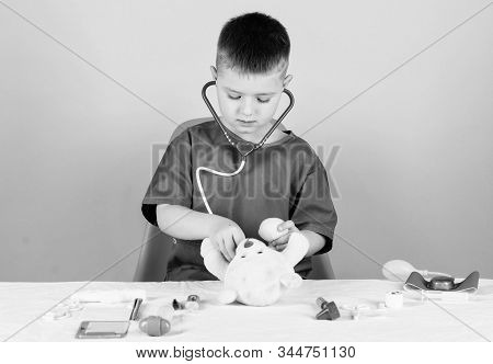 Boy Cute Child Future Doctor Career. Health Care. Kid Little Doctor Busy Sit Table With Medical Tool