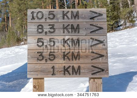 Close-up Wooden Signage With Pointing Distance In Kilometer Snow Forest Background