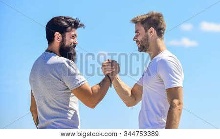 Strong And Muscular Arms. Successful Deal Handshake Blue Sky Background. Men Shaking Hands At Meetin