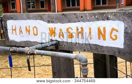 Rustic, Hand Painted Sign Sits Over The Spigots For The Piped In Water.  Orange Handwriting Outlined