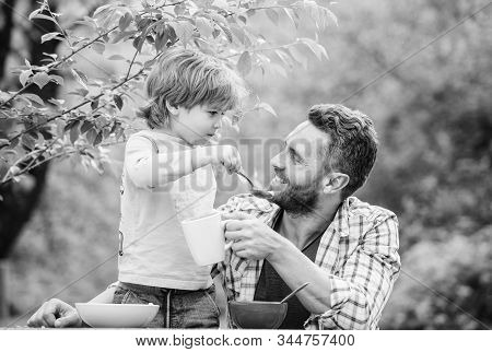 Food Habits. Little Boy With Dad Eating Food Nature Background. Summer Breakfast. Healthy Food Conce