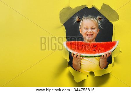 Funny kid eating watermelon outdoors on the yellow backgrounds.  healthy food, girl. torn hole in paper