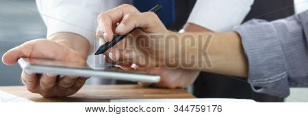 Focus On Colleagues Hands Holding Modern Tablet And Stylos. Businessmen Discussion New Biz Project.