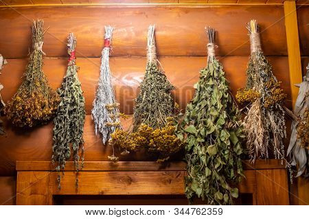 Dried Herbs And Branches On Wooden Background Of Ancient Russian Bathhouse