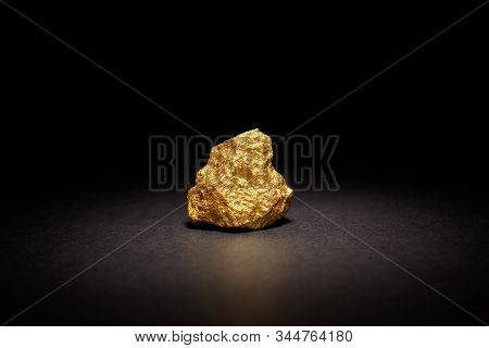 Closeup Of Big Gold Nugget On Black Background. Finance And Business Concept. Gold Ore Found In The