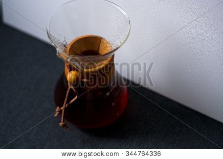 Glass Container Filled With Black Coffee On One-ton White Background With Reflection Of Large And Un