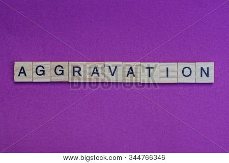 Word Aggravation From Small Gray Wooden Letters Lies On A Lilac Background