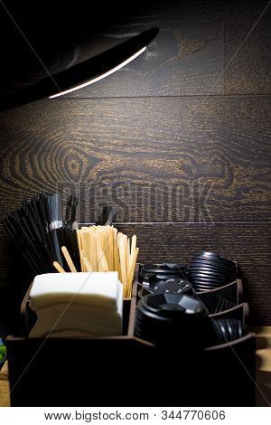 Against Dark Background In The Coffee Shop There Is An Organizer, A Bar Stand For Napkins, Tubes And