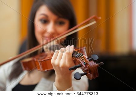 Beautiful woman playing violin in a conservatory