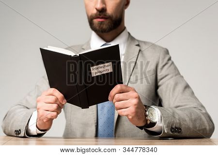 Cropped View Of Businessman Reading Juridical Book With Intellectual Property Title Isolated On Grey