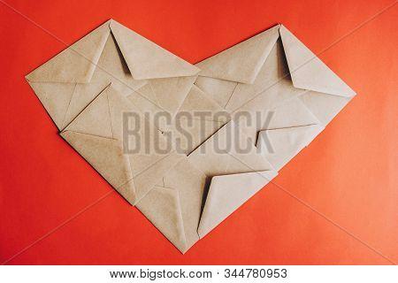 The Heart Of The Letter Envelopes. Kraft Envelopes. Kraft Heart On A Red Background. Happy Valentine