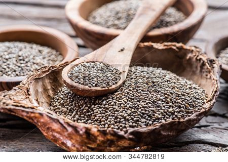 Chia seeds in wooden spoon over organic dish with chia seeds on old wooden table.