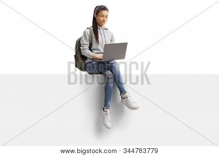 Female student sitting on a blank board and using a laptop computer isolated on white background