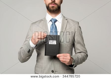 Cropped View Of Businessman Holding Juridical Book With Intellectual Property Title Isolated On Grey