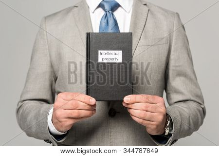 Partial View Of Businessman Holding Juridical Book With Intellectual Property Title Isolated On Grey