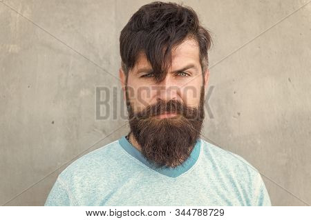 Bearded And Shaggy. Bearded Man With Stylish Haircut On Grey Wall. Unshaven Caucasian Guy Wearing Th