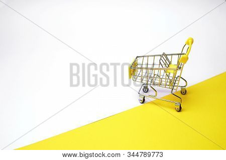 Grocery Basket On Wheels, Minimalism. On Light Background. Online Shopping. Grocery Basket On Wheels