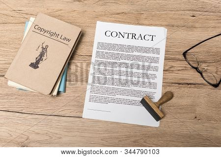 Top View Of Contract, Stamp, Juridical Books And Glasses On Wooden Desk