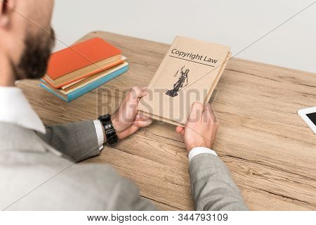 Cropped View Of Lawyer Holding Juridical Book With Copyright Law Title Isolated On Grey