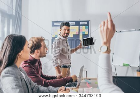 Selective Focus Of Bi-racial Scrum Master Looking At Businesswoman With Raising Hand