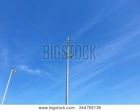 Tall Metal Poles With Street Lights Are Seen From Below. One Pole Has Four Lights, The Other One. Th