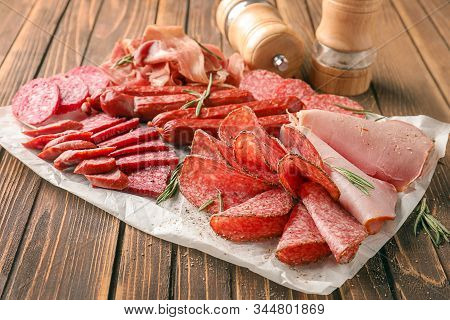 Variety Of Delicious Deli Meats On Wooden Table