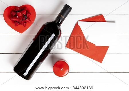 Valentines Day Composition. Heart, Gift, Envelope, Vino Bottle On White Wooden Surface. Valentines D